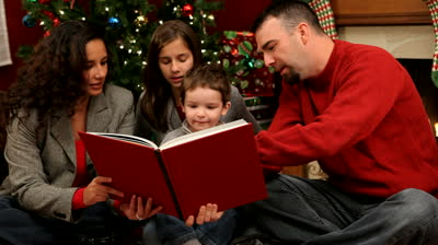 stock-footage-family-reading-a-book-at-christmas-time1